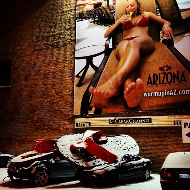 A billboard for Arizona tourism depicts a sunbathing woman whose flipflops have fallen out of the picture to crush a snow-covered car.